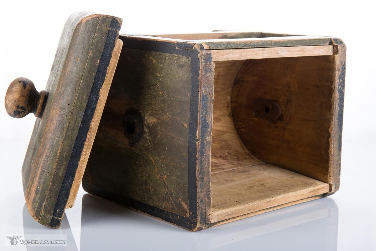 U- formet trommel mellom to rektangulære sideplanker med midtstag imellom. Jernbeslag på hver side for gjennomføring av sveiv. Avrundet lokk med påsatt kant og knott.