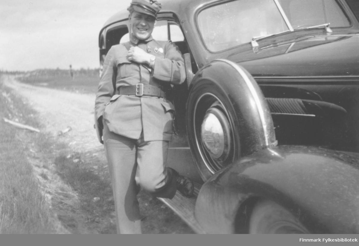Løytnant og sanitetslege Myhre står lent mot en Chevrolet 1937.