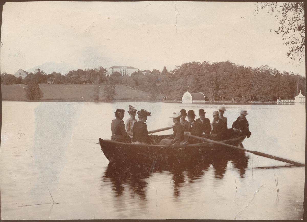 Robåt på innsjø, mennesker, Nääs herregård i bakgrunnen, båthus, badehus