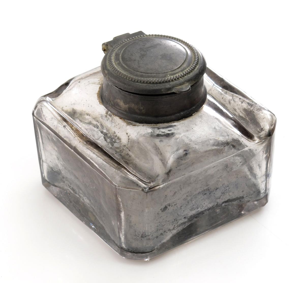 Blekkhus, av glass, forsølvet med tinnlokk.   Kvadratisk blekkhus med rette sider,  flate skuldre med to fordypninger til å legge pennen i, rundt lokk.