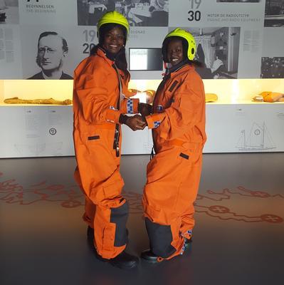 To barn i redningsutstyr, oransje drakter og gule hjelmer.