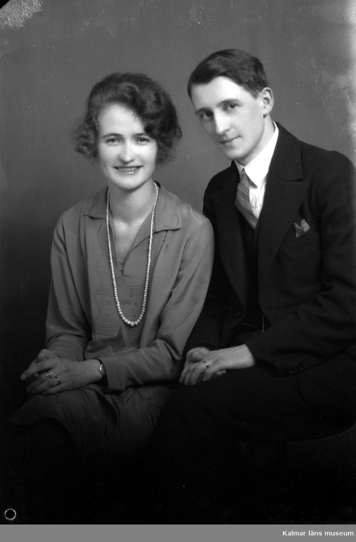 Ateljébild på en kvinna i klänning och halsband. Mannen har kostym. Enligt Walter Olsons journal är bilden beställd av fröken Greta Gustavsson.