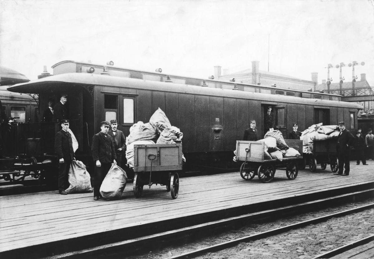 Postvogn som del av togsett. Inn- og utlessing. Posttraller.