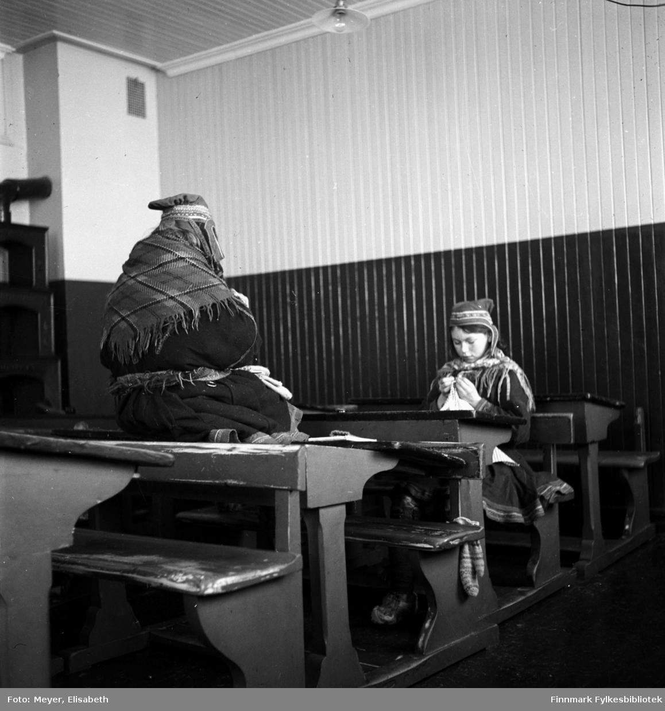 Håndarbeid på Kautokeino Skoleinternat. To jenter sitter og jobber i klasserommet.
