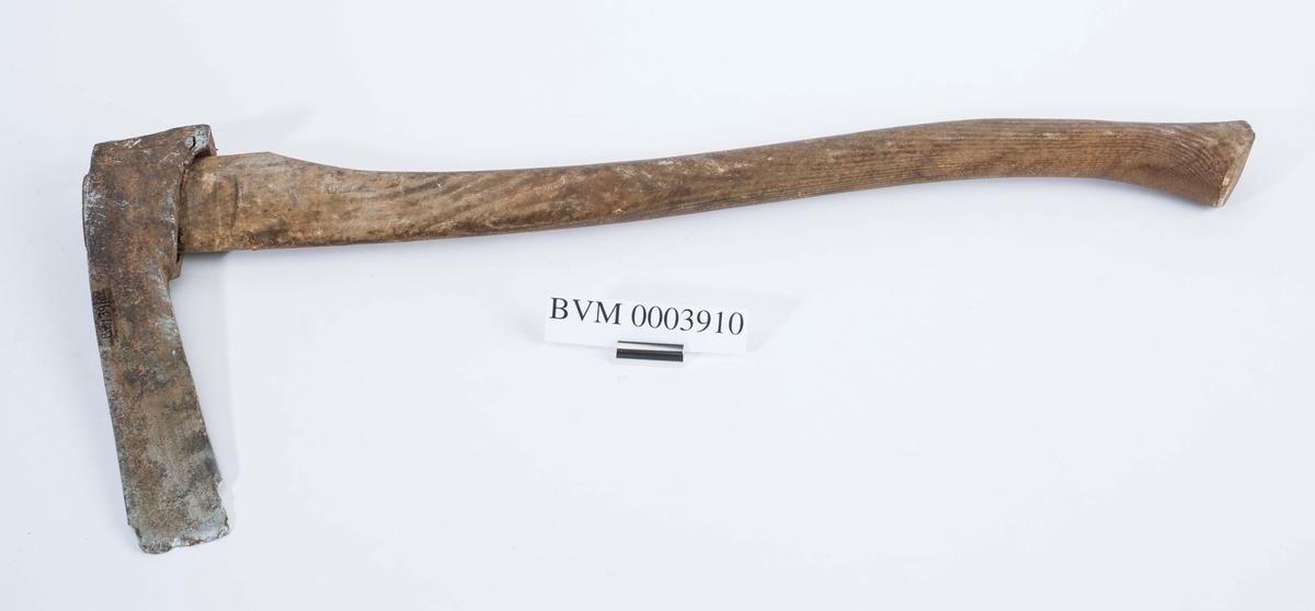 Til å hogge hull i stokker med. Øksehode og skaft. Hodet er 25,9 cmlangt og 6,6 cm høyt.