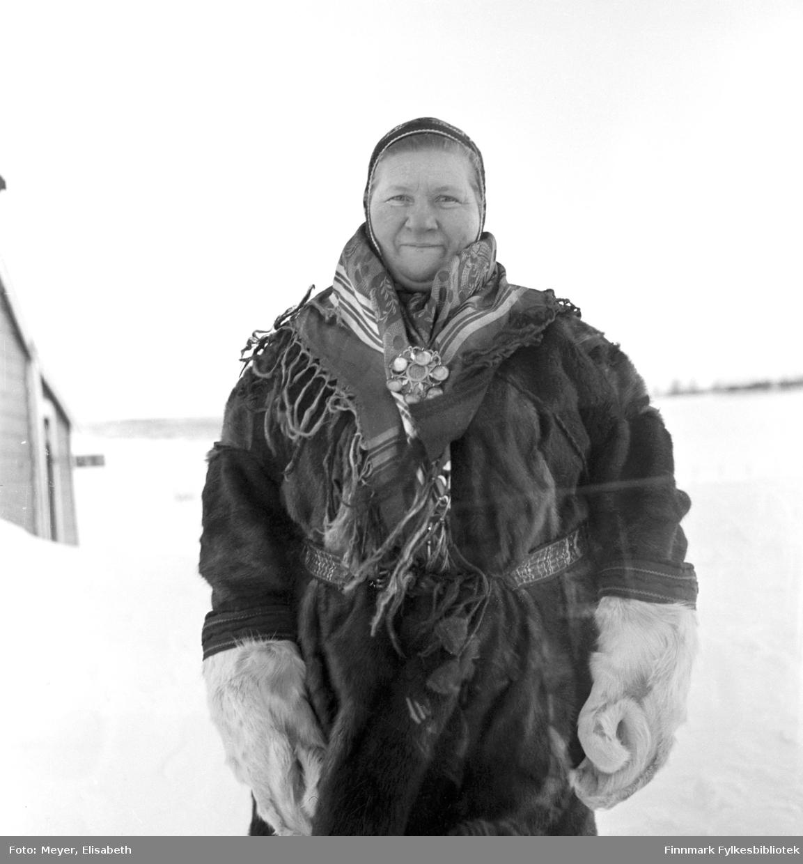 Berit Nilsdatter Hætta fotografert i samisk pesk med samisk sjal med sølje, samiske votter i reinsdyrskinn og samisk lue. Fotografert vinterstid under Elisabeth Meyers besøk i Finnmark.