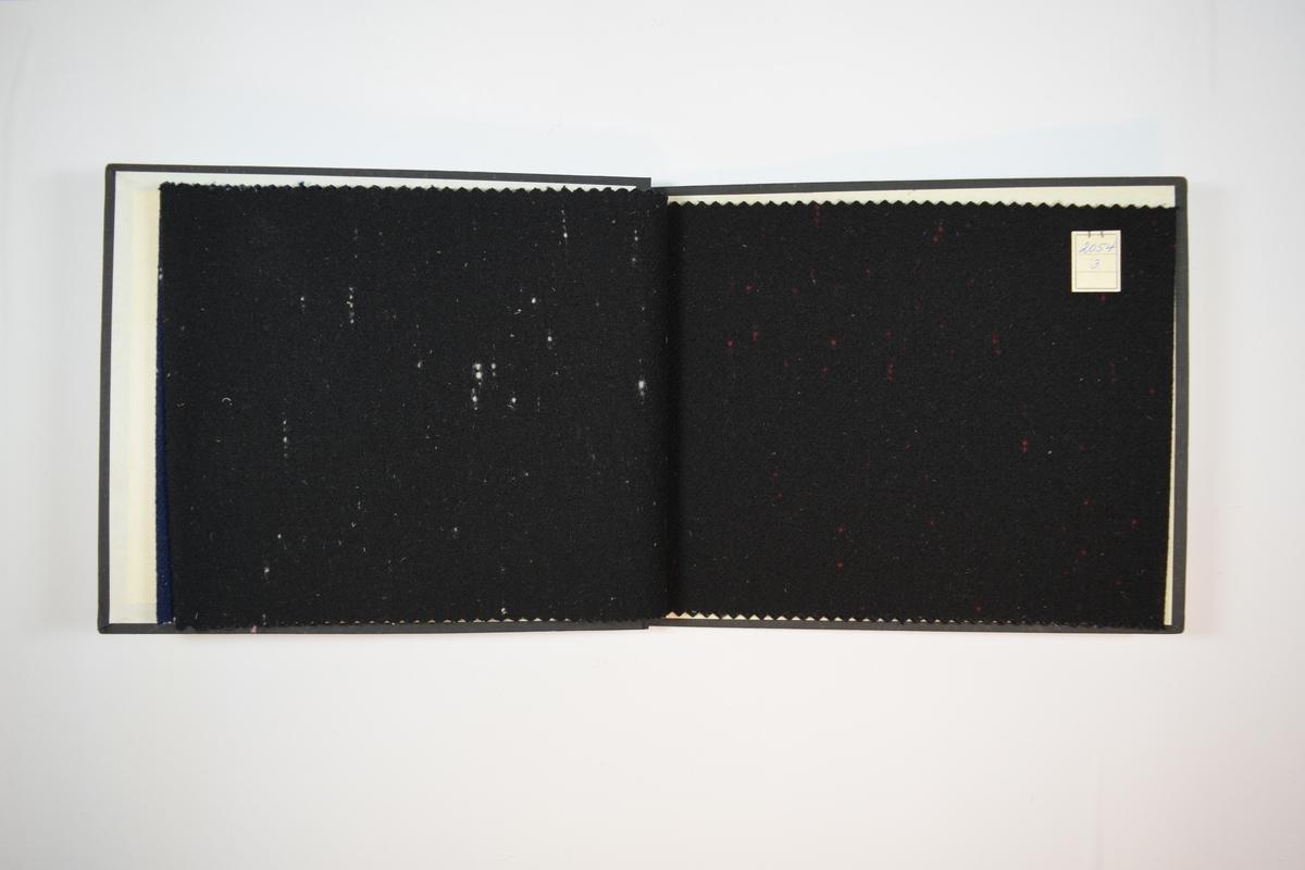 Rektangulær prøvebok med tre stoffprøver og harde permer. Permene er laget av hard kartong og er trukket med sort tynn tekstil. Boken inneholder middels tykke ensfargede stoff med noen korte tråder i andre farger som danner korte stiplede linjer tilsynelatende tilfeldig plasserte.  Kyperbinding/diagonalvevd. Stoffene er merket med en firkantet papirlapp, festet til stoffet med metallstifter, hvor nummer er påført for hånd. Begge lappene har et kryss i nederste venstre hjørne laget med blå kulepenn.   Stoff nr.: 2054/1, 2054/2, 2054/3.