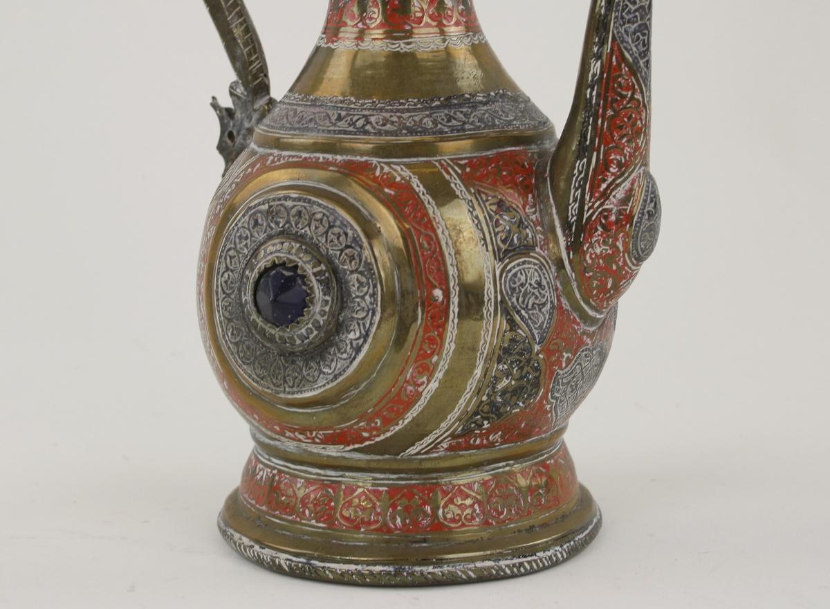 Kanna av mässing med graverad dekor och genombrutet mönster på locket. Försedd med pip. Inläggningar i rött och silver. På sidorna infällda, facetterade blå stenar.Enligt notering från Bokhara, nuvarande Uzbekistan.