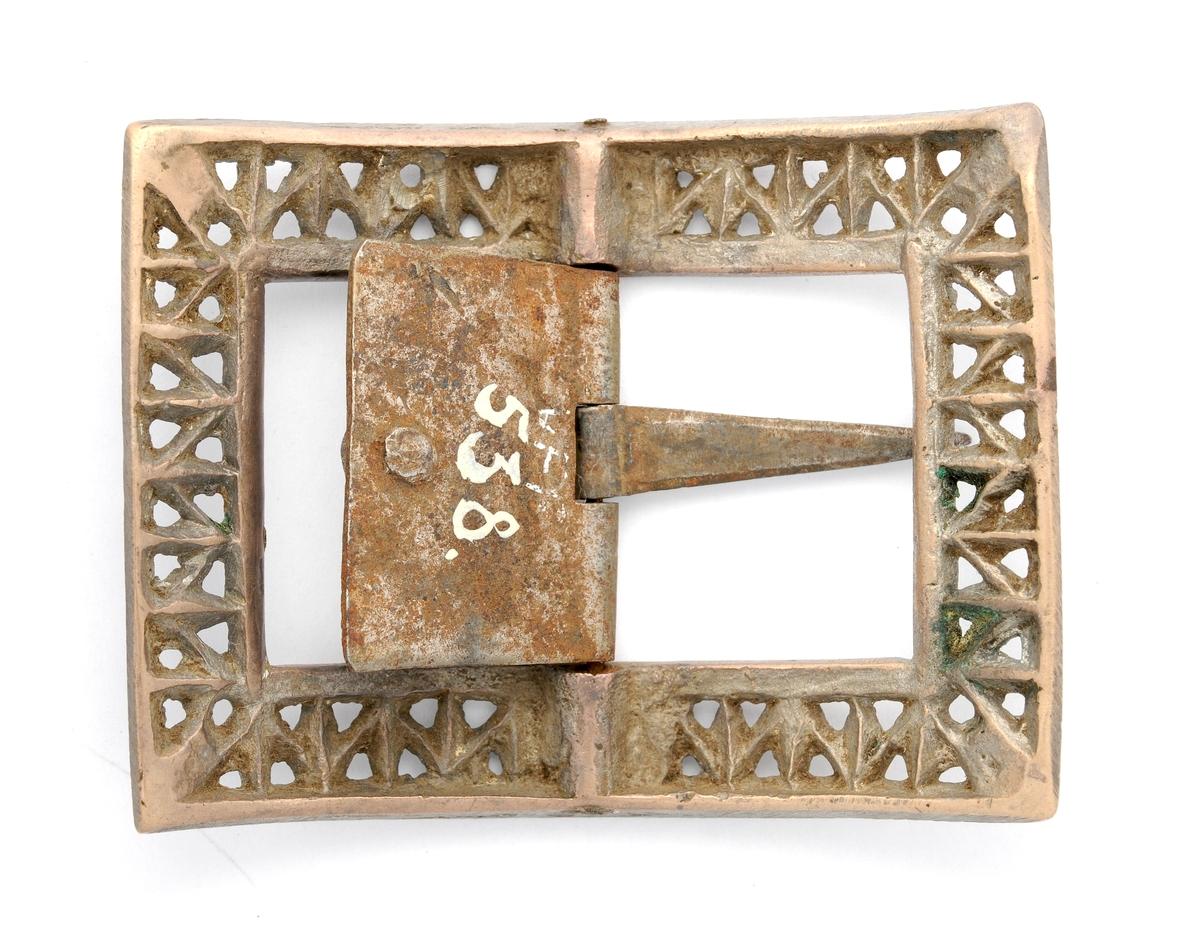 Skospenne i bronse og jern, smidd. Rektangulær form, sterk kuve. Alle fire sider er rette og med ein glatt kant inst og ytst. Mellom desse ei ranke med tverrgåande strek. Mellom rankene ei eggforma skål. Tverrgåande stong med nål og plate.