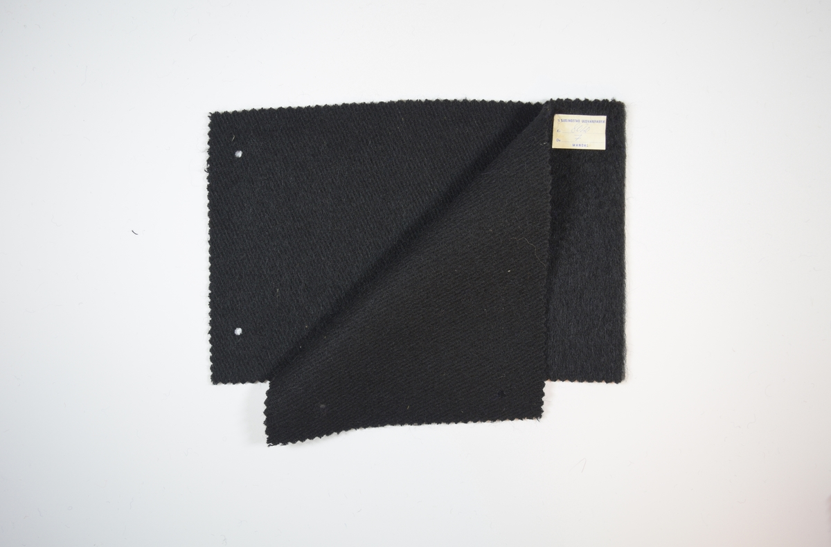 Syv stoffprøver klippet med sikksakk-saks. Middels tykke ensfargede ullstoff . Vevmønsteret kan sees på vranga, men ikke på rettsiden. Kyperbinding/diagonalvevd. Prøvene er brettet slik at formatet blir likt prøvene som finnes i prøvebøker fra Sjølingstad. Alle har to runde hull i margen etter å ha vært/eller skulle bli stiftet til bok eller et hefte. Stoffene er merket med en firkantet papirlapp, limt til stoffet, hvor stoffnummer er trykket i et maskinskrevet skjema.   Stoff nummer.: 8020/1 (antatt, ikke merket), 8020/2, 8020/3, 8020/4, 8020/5, 8020/6, 8020/7.