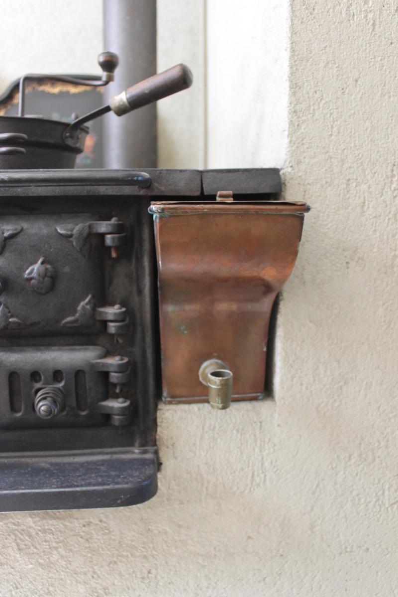 Rektangulär behållare av koppar med två lock i koppar och tappkranshållare av mässing. Tappkranen saknas. Det stora locket tillverkades nytt 1982. Det lilla locket har knopp av rullade kopparband. Cisternen används som vattenbehållare bredvid vedspisen.