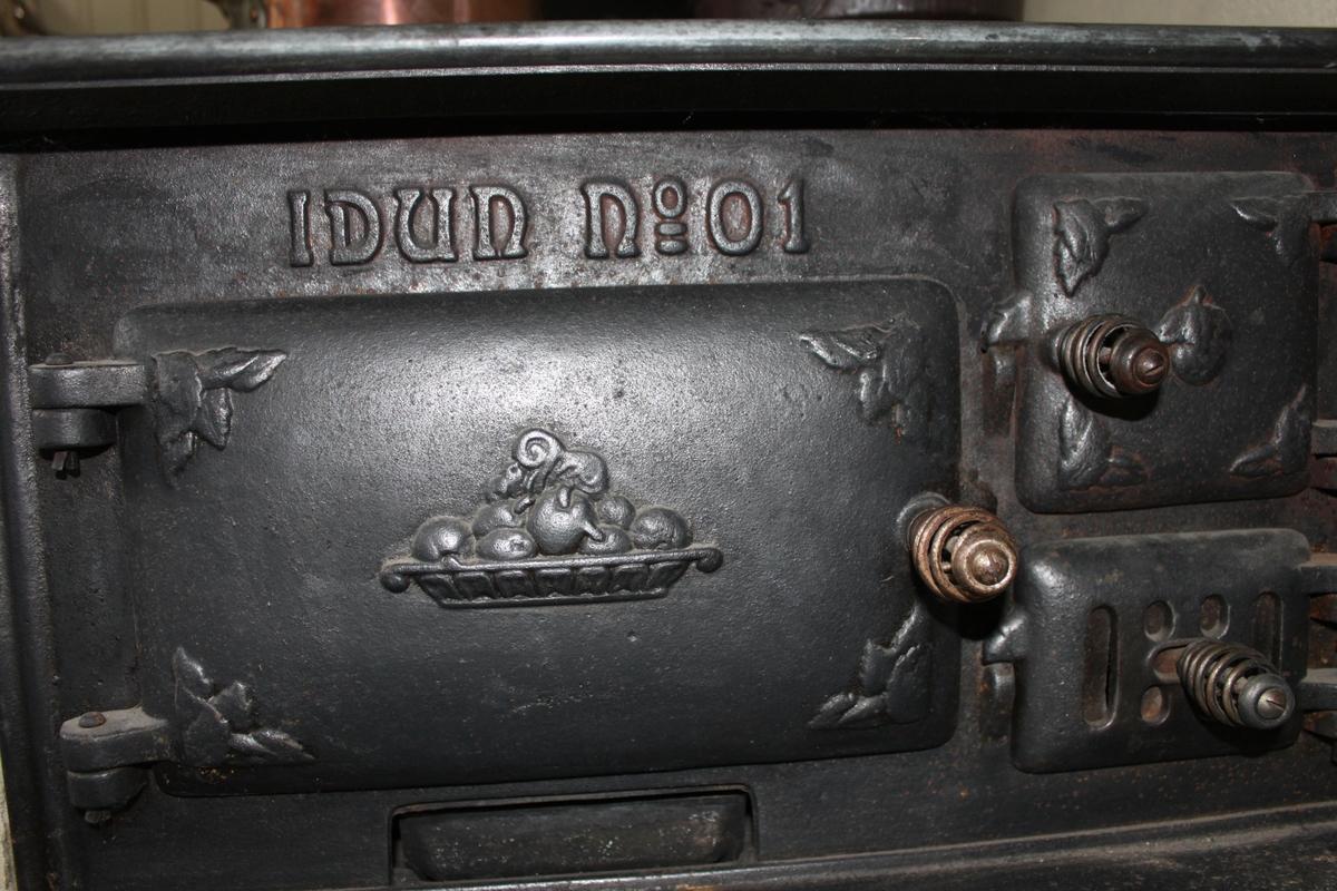 Spis i gjutjärn av märket IDUN No 01. Har tre kokytor, varav två med tre ringar och en med sju ringar. På framsidan finns en större och två mindre välvda luckor. Den stora har motiv av en fruktskål, de mindre av äpple och bladornament.
