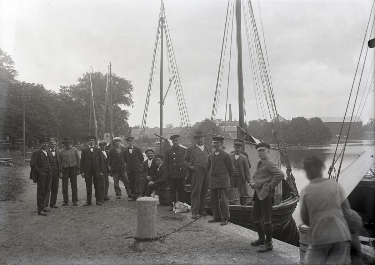 Fotograferingsdatum: den 8 juni år 1924.  S. S. Roxen, boxering av Tasse. Segelbåtar vid Linköpings hamn, Stångån. Hamnen i Linköping.  Personer på bilden från vänster: Isak Andersson (Väderskär), Elof Franzén (Grindö), Karl Andersson (Väderskär), Josef Johansson, Ville Pettersson (Grindö), Elis Söderlund (Väderskär), Gustav Pettersson (Väderskär), Seht Fransén (Grindö), Harald (Halle) Andersson (Trässö), Linköpingsbo?, Linköpingsbo?, Timan Pettersson (Väderskär), Karl Pettersson (Väderskär), Linköpingsbo?.
