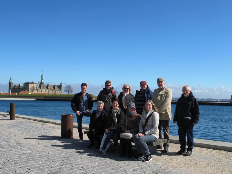 Ti mennesker på og rundt benk i forgrunnen, Kronborg slott ved Øresund, Danmark i bakgrunnen.