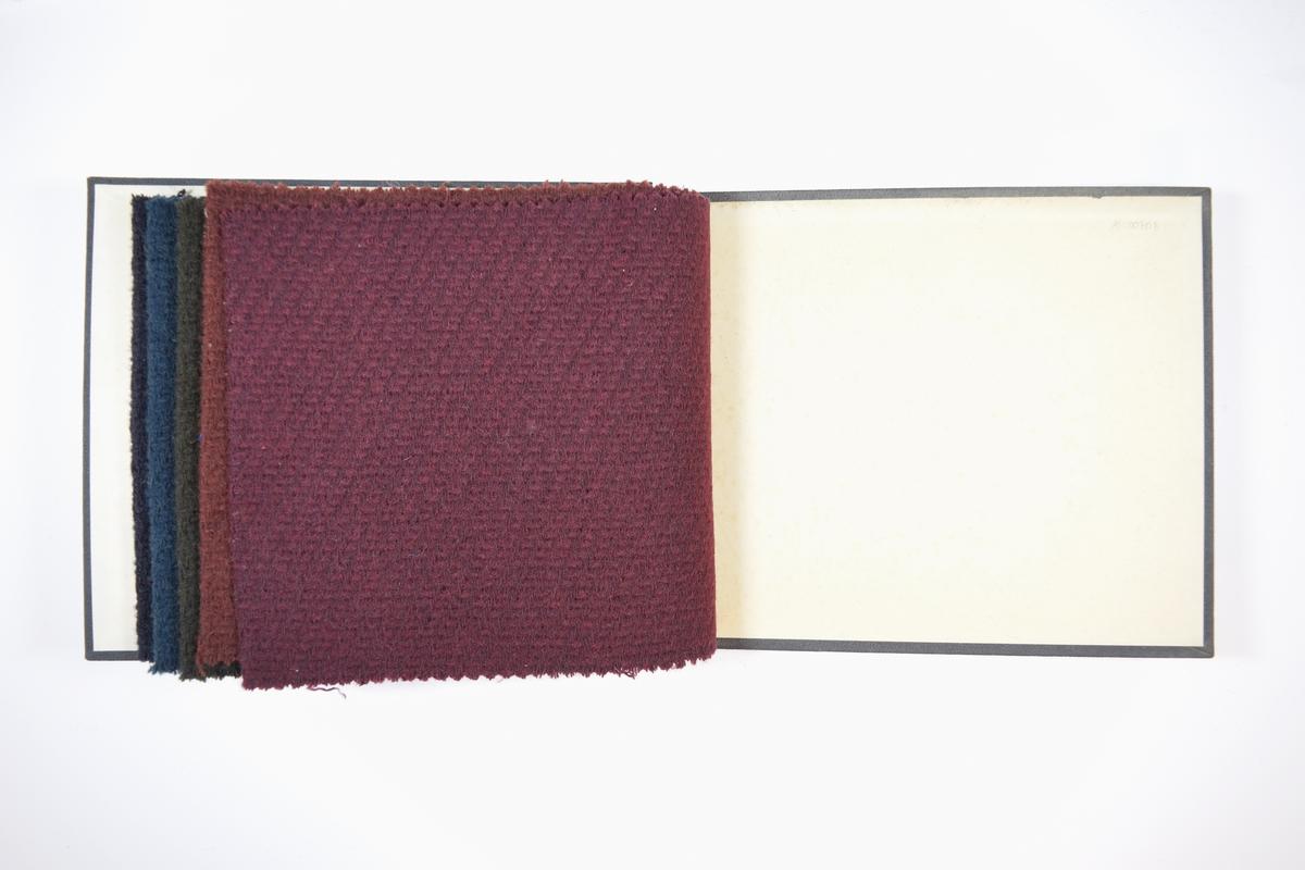 Rektangulær prøvebok med harde permer og fem stoffprøver. Permene er laget av hard kartong og er trukket med sort tynn tekstil. Boken inneholder middels tykke og tette ensfargede ullstoff med diskret skrå striper i vevemønsteret. Kyperbinding/diagonalvevd. Fargene varierer mellom stoffene, men mønsteret er det samme. Stoffene ligger brettet dobbelt i boken slik at vranga skjules. Verken stoffet eller boken er merket med nummer, slik de fleste andre prøvebøker er.  Ukjent/uten stoffnummer.