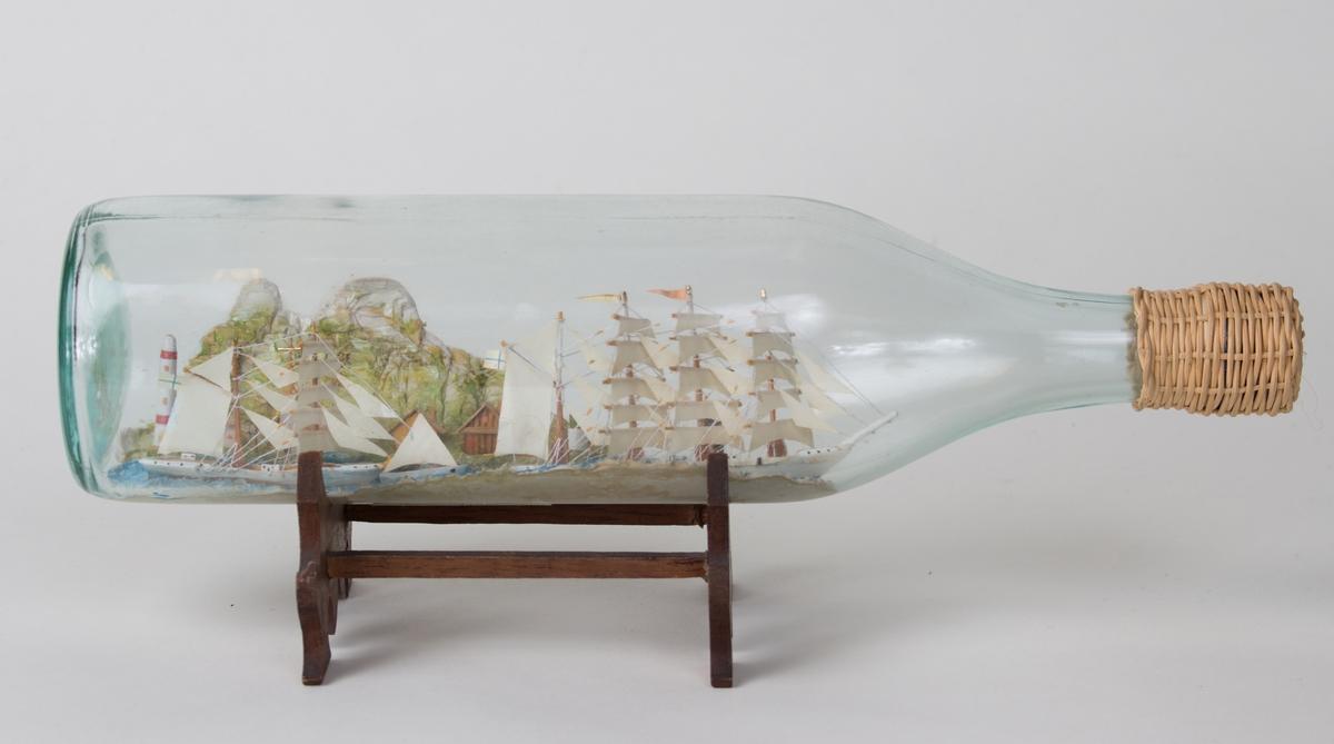 4-mastret bark med seilføring samt to mastret skonner med seilføring og losskøyte med seil. På land sees hus, kirke og fyrtårn.