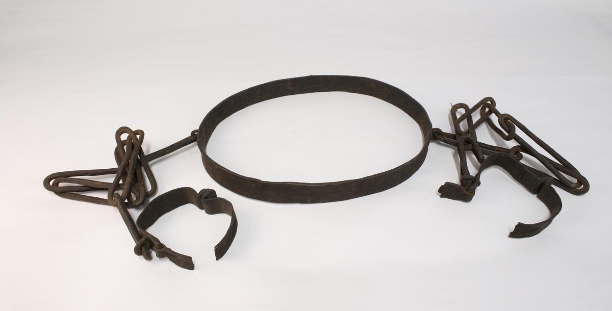 Fangejern, kombinert. Bestående av et livjern som er helsmidd og med største diameter 35 cm. På jernets ene langside er det en hempe. På hver kortside er det en tilsvarende hempe, hvorfra utgår en lenke. Den ene lenken er 81 cm lang og den andre 76 cm. Den korteste lenkens nederste ledd er bøyet i en vinkel på  ca. 150 grader.  Hvor lenken består av 7 ledd. Til hver lenke-ende er smidd et hengselet fotjern som er klinket sammen. forjernet er brutt i stykker.