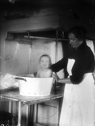 Tora Alinder badar Tore Alinder i balja på bord i köket, Säv