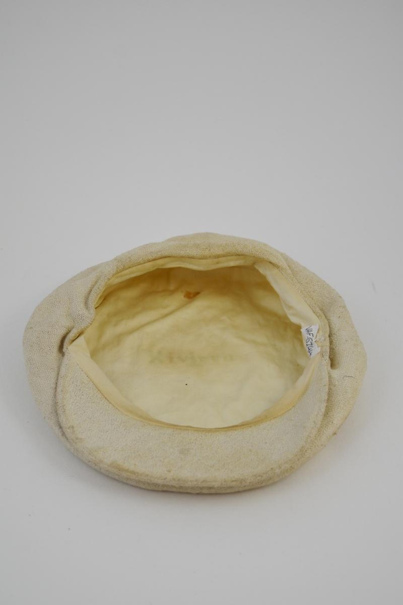 """Oval form, """"alpeluefasong"""" m/innfelt stykke midt foran hvor også bremmen sitter, avstivet. En rusten trykknapp på bremmen regulerer fasongen på luen. Foret."""