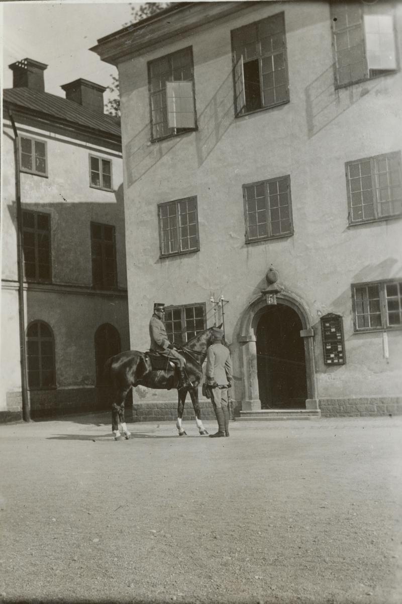 En officerare på häst möter en soldat utanför Militärhögskolan Karlberg.