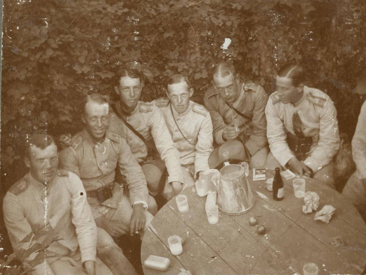 En grupp soldater kring ett bord i trädgården. På bordet finns bland annat en mjölkanna, ett antal glas och två äpplen.