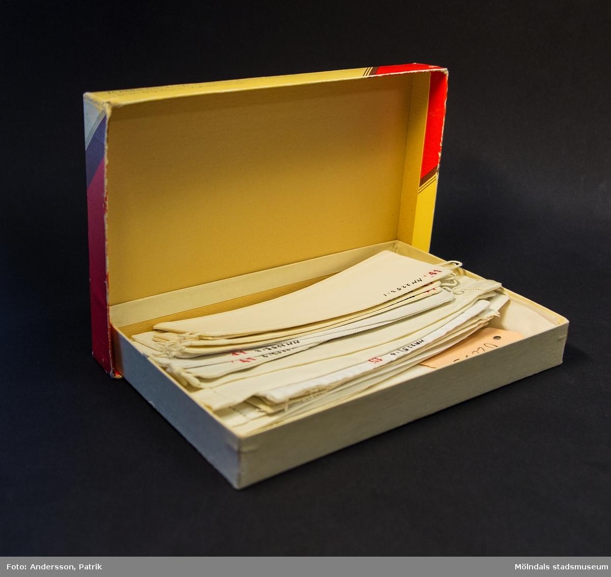 Chokladask med lock av papp. Gul kartong med röda, bruna och guldfärgade detaljer samt en ros. Text i rött: Cloettalogo, i brunt och guld: BRISTOL PRALINER. På undersidan asken finns en etikett: 1039 BRISTOL, Innehåller Roxy-praliner, Nettovikt 250 gr, Konsumentpris 2:40. Kartongen med tillhörande lösmanchetter (02253:1-12) har använts av vårdarinnan Karin Hasselberg på Stretered.