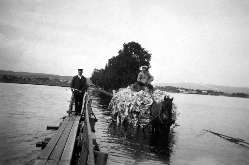 Svart-hvitt foto fra 1927. Gangbru med mann og hestetransport med stort lass som kjører på ordinær bru i flomvann. (Foto/Photo)