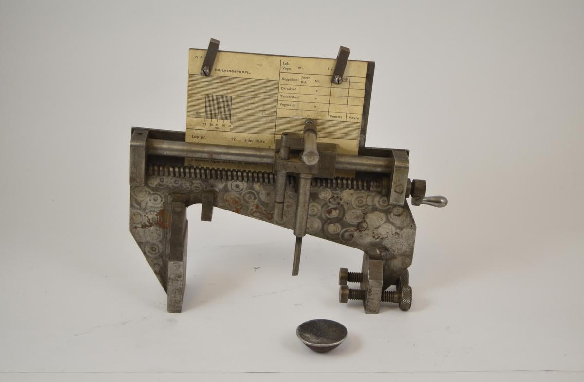 Skrivende hjulmålingsapparat. Man monterer blyant og skjema i apparatet, apparatet festes på hjulet, en kurve av hulet tegnes inn på skjema. Brukt til å måle hjul slitasje. Når hjulet var slitt måtte det til verksted for å opprette original hjulprofil.