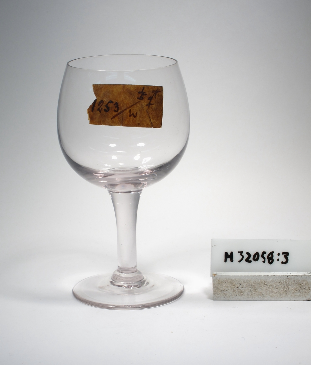 """Äggformad kupa med påklipprt koniskt ben ned mot foten. Etikett: Lapp: """"1/5 ??"""" """"1253/W"""""""