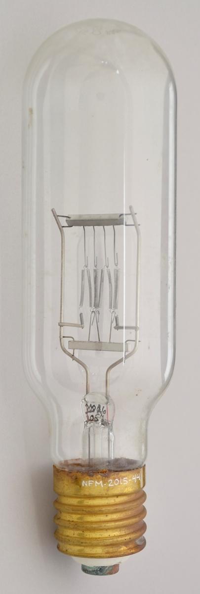 Stor lyspære innpakka i silkepapir og bølgjepapp. Lyspæra er ubrukt. GJennomskineleg glas. Messingsokkel. 1000 W.