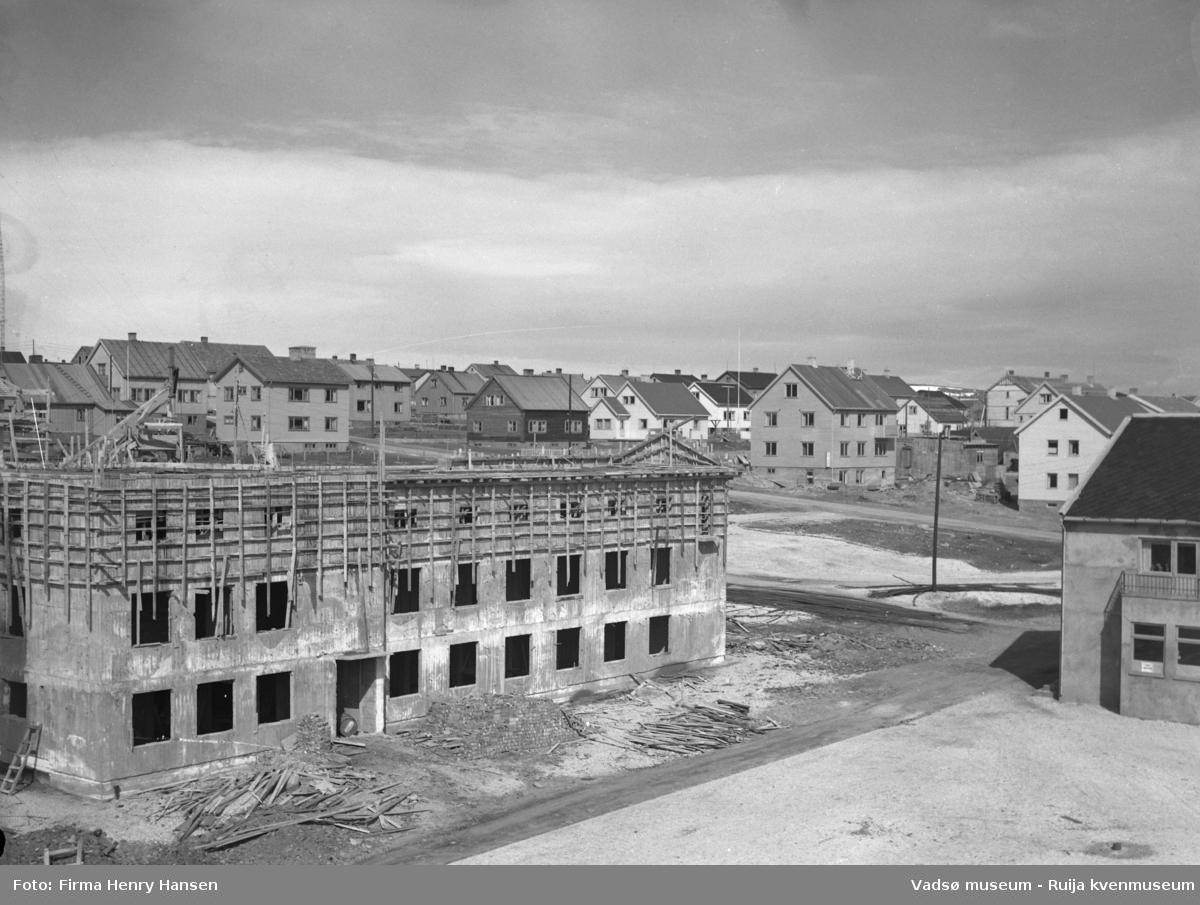 Vadsø 3.6.1951, Sentrum. Bildet er tatt fra sørvest, motivet er først og fremst Rådhuset under bygging. Fasaden mot sør er påbegynt, første og andre etasje er ferdig murt med åpninger for vinduer, i tredje etasje er forskalingen på. Bildet viser en del av torget, og en del av baker Henriksens bygg vises til høyre i bildet.