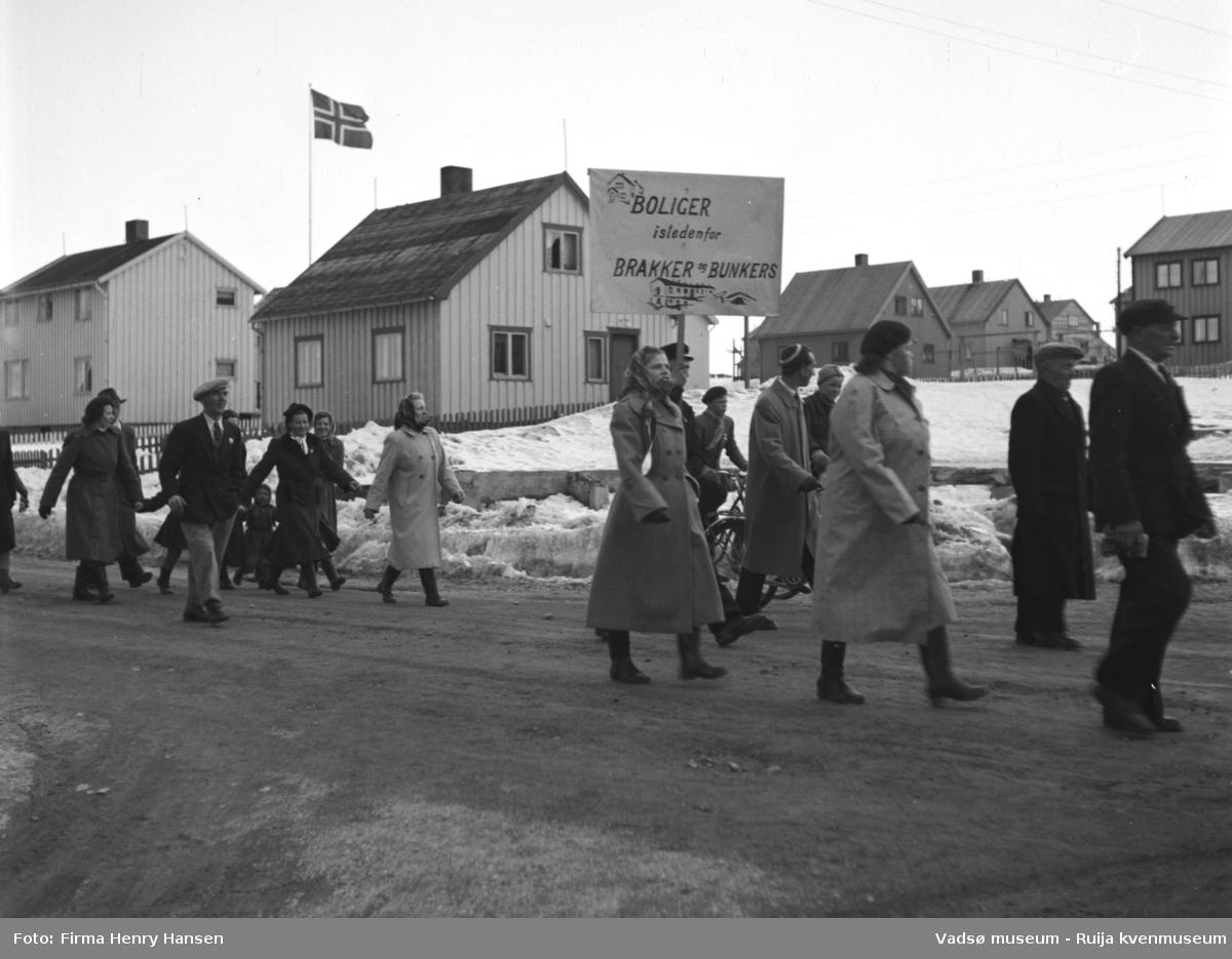 """Vadsø 1.mai 1952, Oscarsgata. Huset midt i bildet er Natalie Øyens bolig. Folk, kvinner, barn og menn, går i tog. En mann bærer en plakat med tekst """"Boliger istedenfor brakker og bunkers"""" . På plakaten er det også to tegninger av hus. I bakgrunnen ser vi flere bolighus, flaggstang med norsk flagg ved ett av husene. Det er snø på bakken."""