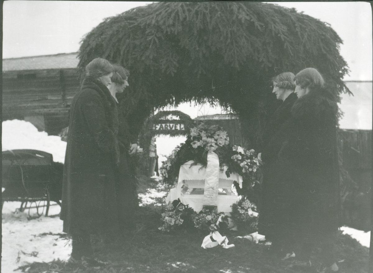 Gravferd etter Anders Juven. Kista er plassert i ein barsal. Hans fire døtre står rundt kista.