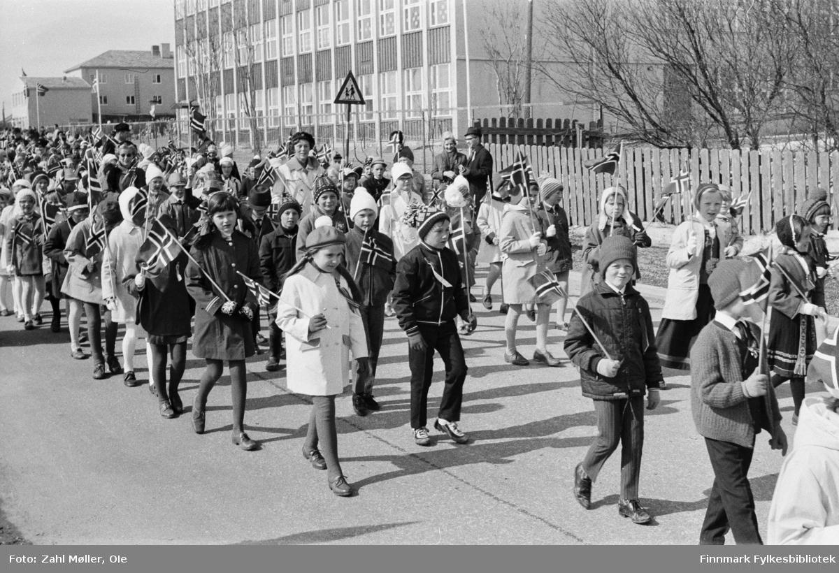Vadsø 17.5.1969.  Fotoserie av Vadsø-fotografen Ole Zahl-Mölö. Barnetoget passerer med barn som holder 17.mai flagg, mange i sin fineste stas med kåper og 17.mai sløyfer festet på brystet.