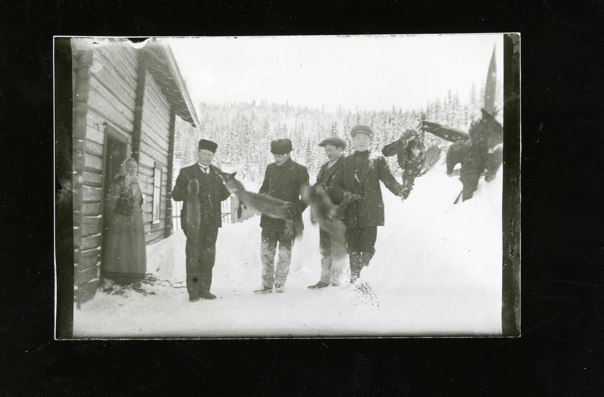 Utanfor kårbygningen på Lundene. I døra står Ingebjørg Lundene. Frå venstre Ole Andreas, Lundene, Olaf Langedrag, Kristoffer Lundene og Ola Lundene.