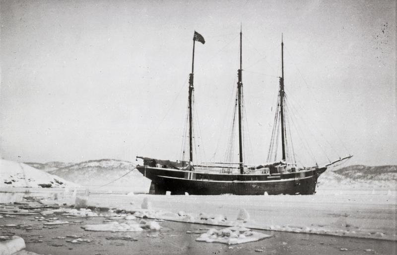 Svart-hvitt bilde av skonnert med tre master i isen.