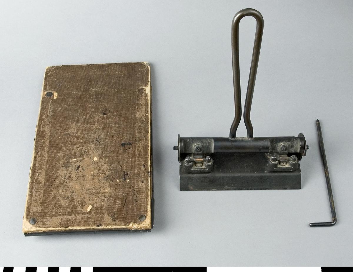 Hålslag av stål och papp. Instansat: TENGWALL HELSINGBORG SWEDEN  Funktion: Mekanism för att göra hål i papper, för pärmförvaring