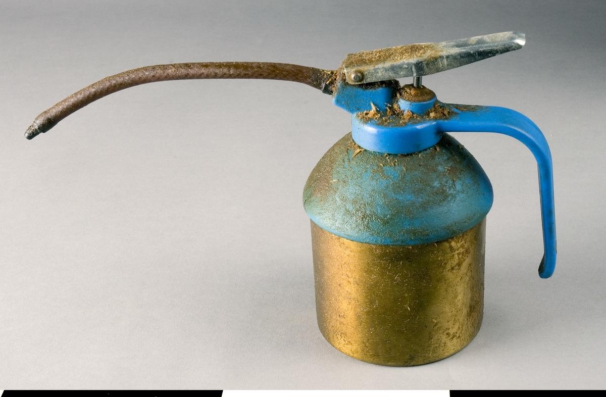 Oljekanna av mässing och stål. Kannans cylindriska underdel är tillverkad av mässing och överdelen av blålackerat stål. Pipen är flexibel och av plast. Pumphandtaget sitter i centrum av överdelen. Handtaget på sidan är öppet nedtill. Oljekannan är ett senare inköp och kan vara från 60-80-talet. Kannan fungerar och används vid smörjning av maskiner på snickerifabriken.  Funktion: Förvaring och utdelning av smörjolja