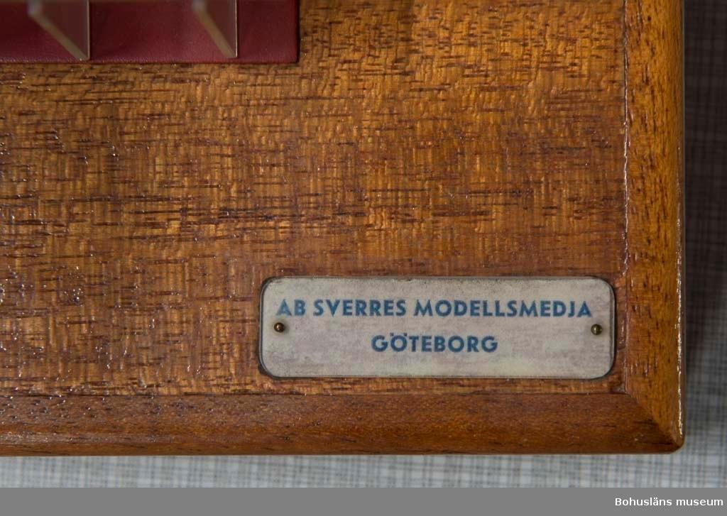 """Modell av sektion till bulklastbåt stående på en träsockel. Färgen är röd och grön + genomskinlig plast. Märkningar på båda sidor på sockeln: """"AB Sverres modellsmedja Göteborg""""."""