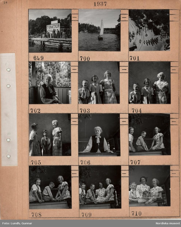 """Motiv: Personer på en kaj av trä framför en stor skylt med texten """"Tomter till salu"""", mindre segelbåt på en sjö, fågelperspektiv på gatukorsning i stad med fotgängare, cyklister och bilar, äldre kvinna sitter på en veranda med spaljé och klätterväxt, två flickor och en pojke klädda i finkläder, äldre kvinna vid verandaräcke, två flickor och en pojke med sin mamma(?) på veranda."""