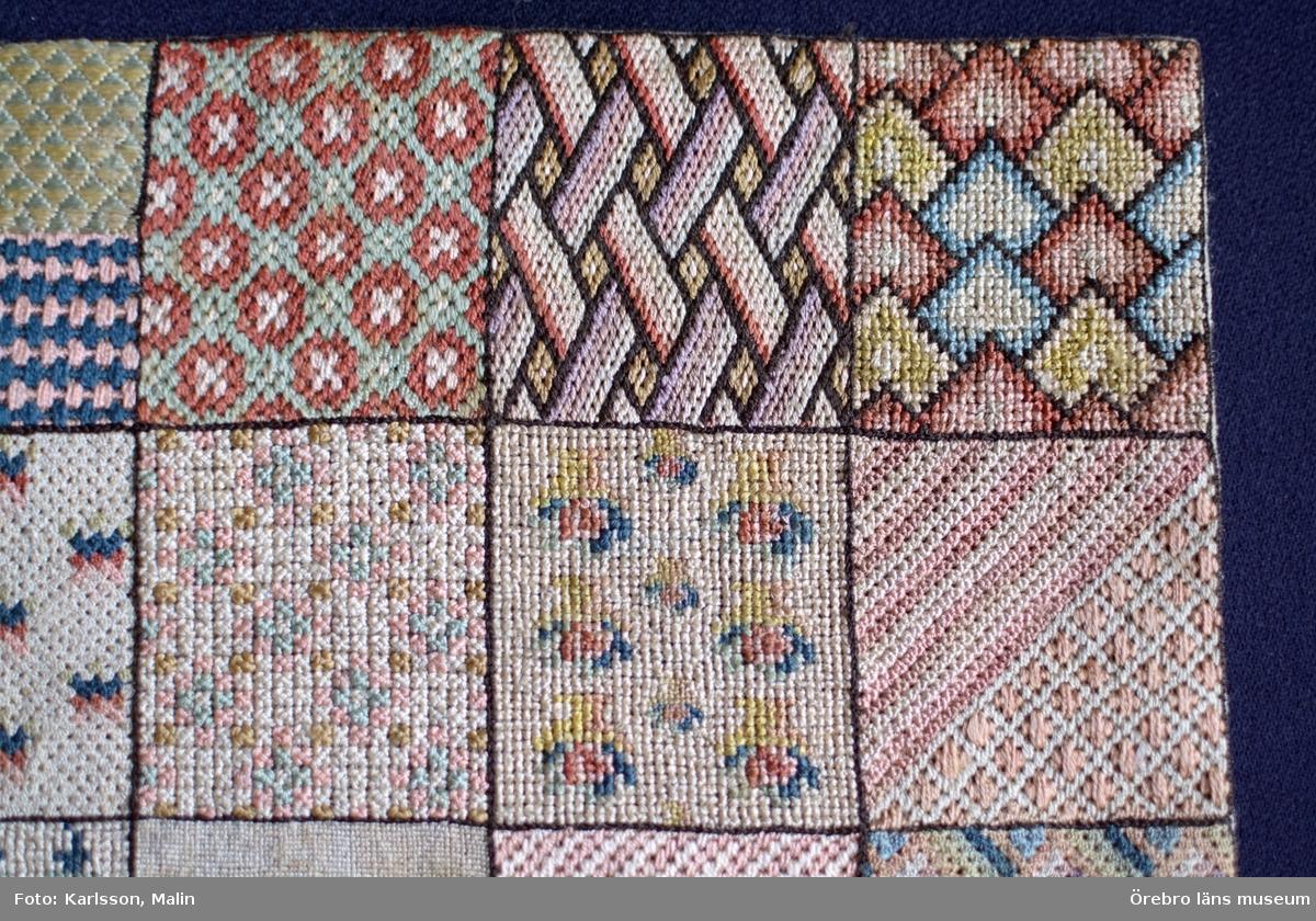Broderad märkduk bestående av 36 kvadrater med olika mönster.