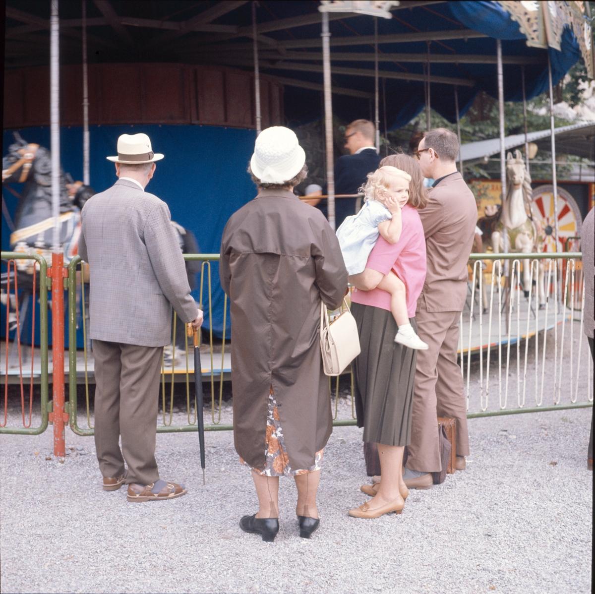 En grupp personer betraktar en karusell. Ett barn betraktar något som är mer spänande och som inträffar utanför bilden.