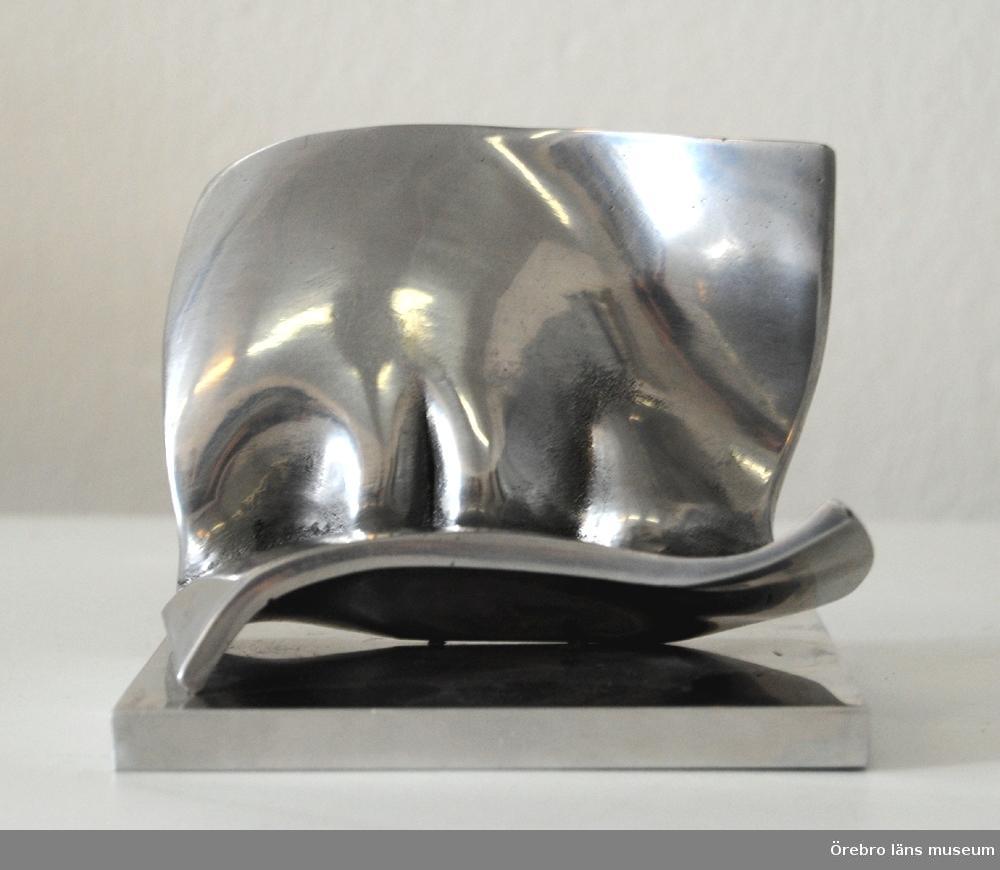 """Aluminiumskulptur """"Kind"""".En fyrkantig aluminiumplatta (5 mm tjock) är böjd vid 2/3 av bredden och """"veckad"""" vid böjningen där den är fäst vid en bottenplatta.Anm: inköp i juni 1974 i samband med Barbro Bäckströms utställning på Konstfrämjandet i Örebro. Pris 400 kr.Digitalbild finns."""