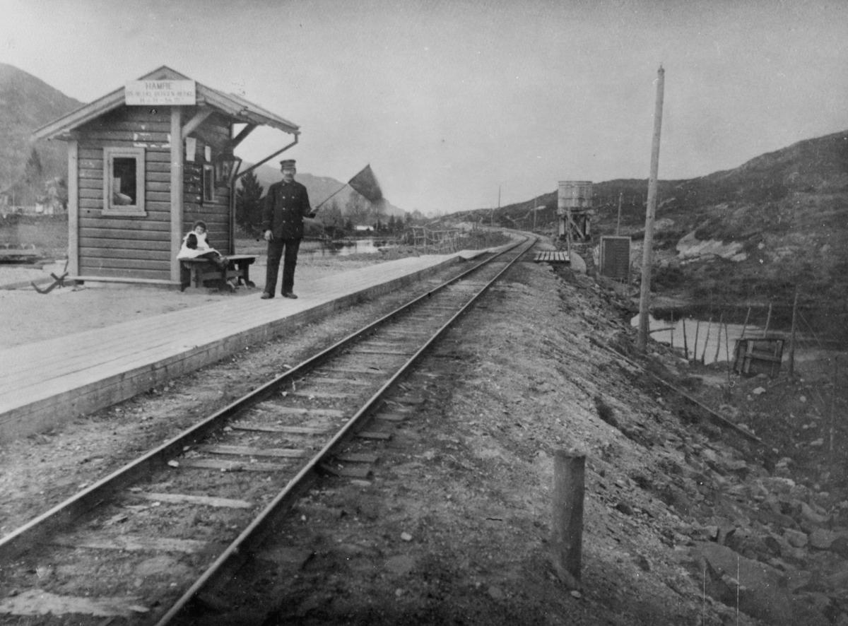 Hamre stasjon på Nesttun-Osbanen. Banevaktar Olaf Fredriksen med flagg. Dottera hans, Magda (f. 1896), sit på benken.