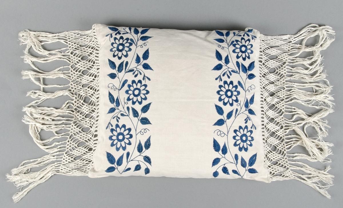 Kuddar av vitt linne med breda, gallerknutna fransar av bomullsgarn. Broderade blomrankor med molinégarn i rosa på den ena, blått på den andra kudden. Plattsöm och stjälksöm.