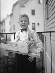 Gutt med heimelaga lastebil av tre, kvit skjorte og sløyfe,