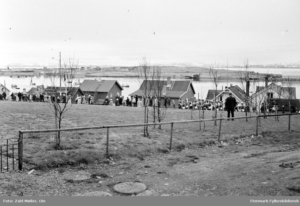Vadsø 1968, Sangen og Musikkens Dag. Korps og sangere går i prosesjon. Bildet er tatt på avstand. Mann med hatt står og betrakter det hele.