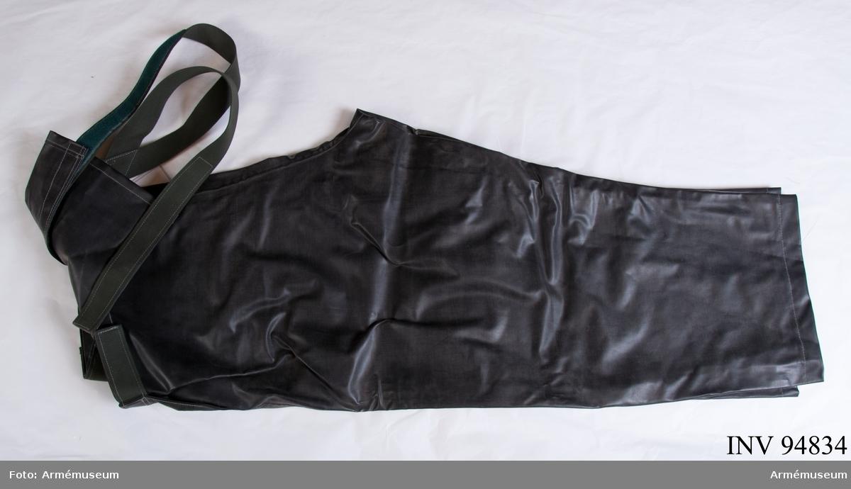 """Svarta skyddsbyxor i plastbelagd väv, med kardborreknäppning och hängslen. Bröstlappen saknar fodring. Vidhängande etikett: """"Försvarets materielverk, Fastställs, M 7370-241000-5, Skyddsbyxor oljeb, 1986-06-01 (oläslig underskrift), FMV 267.3. (FMV:Bekläd) 85-09. 1000 Ex"""". På insidan: """"Får ej användas vid cisternrengöring""""."""
