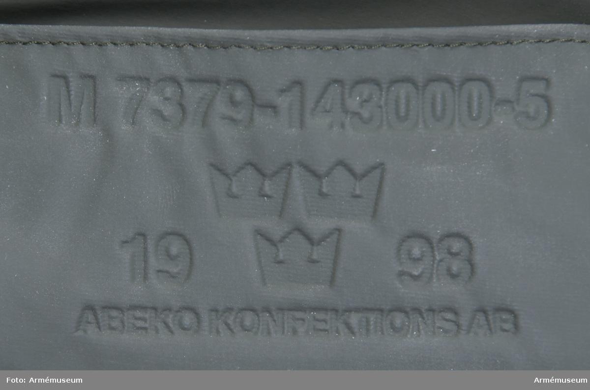 """Regnjacka i olivgrön plastbelagd väv. Vidhängande etikett: """"Fastställd modell, M 7379-143000-5, Regnställ jacka 90 B, Teknisk bestämmelse 11623 B, Vapenslag A, M och FV (ikryssade rutor), datum 1999-04-20, Bo Waltersson försvaret materielverk datum: 1999-04-20 Liskulla Wigardt"""". Präglat på utsidan vid knäppningen: """"M 7379-143000-5, 1998, Abeko konfektions AB""""."""
