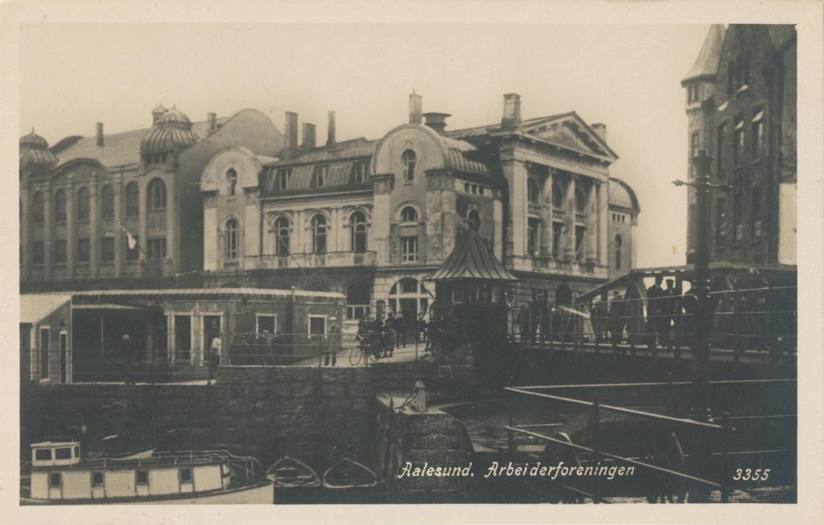 Prospektkort fra Arbeiderforeningen i Ålesund sett fra andre siden av Brosundet.